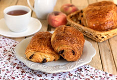Chocolate croissants with tea for breakfast. Chocolate croissants (pain au chocolat) with tea for breakfast royalty free stock photography