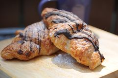 Chocolate croisssant pastry close up. Chocolate drizzled baked croissant on wooden cutting board with mug Royalty Free Stock Photos