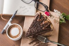 Chocolate crunch cake with hot macchiato and glasses, pen and book background stock photos