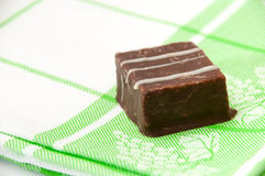 Chocolate cubes on a green kitchen tablecloth Royalty Free Stock Photography