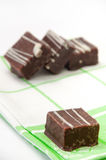 Chocolate cubes on a green kitchen tablecloth Royalty Free Stock Images
