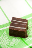 Chocolate cubes on a green kitchen tablecloth Stock Photo