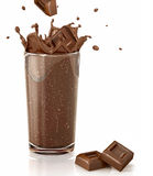 Chocolate cubes splashing into a choco milkshake glass. Royalty Free Stock Images