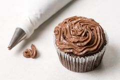 Chocolate cup cake with piping bag on the white marble background Royalty Free Stock Photography