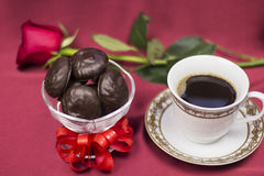 Chocolate and a Cup of coffee on a background of red roses Stock Photos