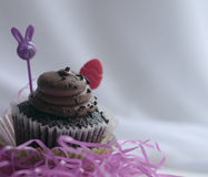 Chocolate cupcake with blurred Easter objects Royalty Free Stock Images
