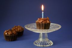 Chocolate cupcake with a burning candle on a glass bowl, two more on the side, deep blue background with copy space. Selected focus, narrow depth of field royalty free stock photo