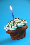 Chocolate cupcake with candle. And blue frosting Stock Photography