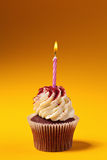 Chocolate cupcake with candle  on orange Royalty Free Stock Photography