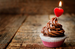 Chocolate cupcake with a candle in the shape of a heart Royalty Free Stock Images