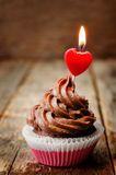 Chocolate cupcake with a candle in the shape of a heart Stock Images