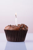 Chocolate cupcake with a candle on a white background Royalty Free Stock Image