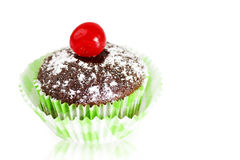 Chocolate cupcake with cherry on white. Delicious chocolate cupcakes topped with powdered sugar and maraschino cherry over white reflective background as copy Stock Images