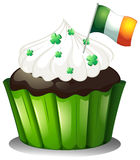 A chocolate cupcake with clover plants and the flag of Ireland Royalty Free Stock Photography
