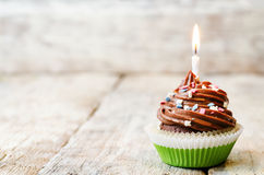 Chocolate cupcake with colorful sprinkles with candles Royalty Free Stock Photos