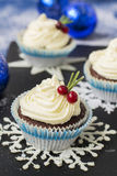 Chocolate cupcake with cream cheese in Christmas decorations.  Royalty Free Stock Photo
