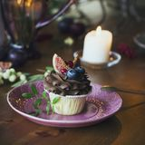 Chocolate cupcake with figs and berries on festive table. Chocolate cupcake with figs and berries on the festive table Royalty Free Stock Photos