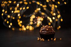 Chocolate cupcake with golden candies and burning sparkler on dark wooden background against blurred lights. Selective focus. Unhealthy food or holiday stock photo