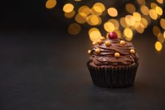 Chocolate cupcake with golden candies on dark wooden background against blurred lights. Selective focus. Unhealthy food.  royalty free stock image
