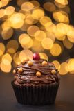 Chocolate cupcake with golden candies on dark wooden background against blurred lights. Selective focus. Unhealthy food.  royalty free stock photo