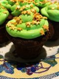 Chocolate cupcake with green frosting and golden stars sprinkles on a white mosaic-patterned plate stock photos