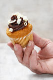 Chocolate cupcake in hand Royalty Free Stock Images