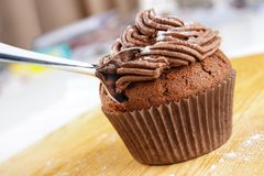 Chocolate cupcake. Home baked chocolate cupcake with icing and spoon in it Stock Photos