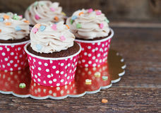 Chocolate cupcake with mousse cream icing on grunge dark wooden background copy space Royalty Free Stock Photography