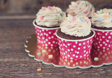 Chocolate cupcake with mousse cream icing on grunge dark wooden background copy space Royalty Free Stock Images