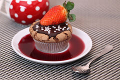 Chocolate cupcake muffin on white plate with a strawberry syrup or wine Stock Photography