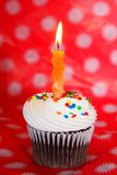 Chocolate cupcake with orange wavy candle Stock Photography