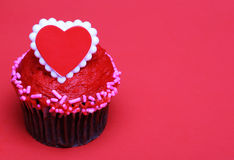 Chocolate cupcake with red heart on the top, over red background Royalty Free Stock Photo