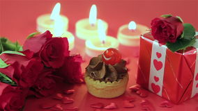 Chocolate cupcake with roses and gift at candlelight. Chocolate cupcake against a red background with roses and gift at candlelight for a bright, fun and stock footage