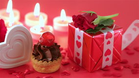 Chocolate cupcake with roses and gift at candlelight. Chocolate cupcake against a red background with roses and gift at candlelight for a bright, fun and stock video footage