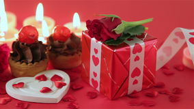 Chocolate cupcake with roses and gift at candlelight. Chocolate cupcake against a red background with roses and gift at candlelight for a bright, fun and stock video