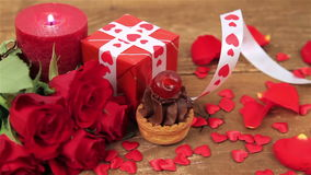 Chocolate cupcake with roses and gift on wood stock footage