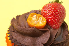 Chocolate cupcake with strawberry. Chocolate cupcake with icing, fresh strawberry and orange rind on yellow background Royalty Free Stock Photography