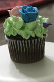Chocolate cupcake topped with Green frosting, and Blue and Pink sugar roses Royalty Free Stock Image
