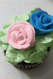 Chocolate cupcake topped with Green frosting, and Blue and Pink sugar roses Stock Photography