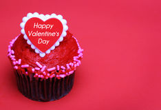Chocolate cupcake with Valentines heart on the top, over red Stock Images