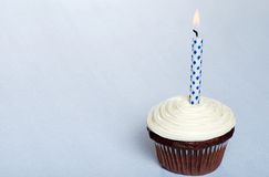 Chocolate cupcake with vanilla frosting and candle Stock Photos