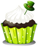 A chocolate cupcake with a white icing and a green hat Stock Photography