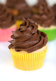 Chocolate cupcake in yellow wrapper. Cupcake with swirled chocolate frosting in yellow wrapper Stock Photo