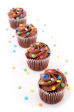 Chocolate cupcakes. Mini chocolate cupcakes with colorful sprinkles on white background Royalty Free Stock Photos