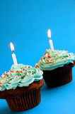 Chocolate cupcakes. With candles and blue icing stock image