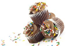 Chocolate Cupcakes. Delicious chocolate cupcakes with chocolate frosting and sprinkles stacked in corner on white background, diagonal with copy space selective Royalty Free Stock Images