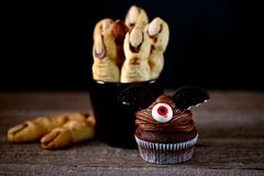 Chocolate cupcakes `bats` and shortbread cookies `witch`s fingers` - delicious bakery sweets for the celebration of Halloween. Royalty Free Stock Photo