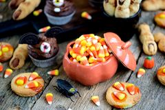 Chocolate cupcakes `bats` and shortbread cookies `witch`s fingers` - delicious bakery sweets for the celebration of Halloween. Stock Photos