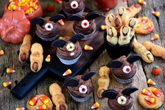 Chocolate cupcakes `bats` and shortbread cookies `witch`s fingers` - delicious bakery sweets for the celebration of Halloween. Food Royalty Free Stock Photos