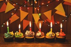 Chocolate cupcakes with candles against festive background Royalty Free Stock Photography
